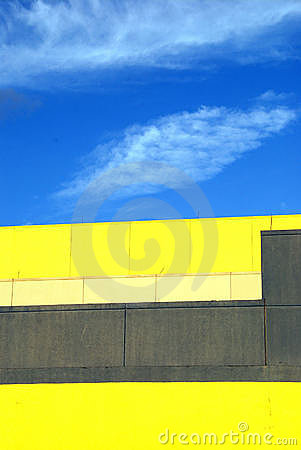 Yellow building against blue sky and clouds