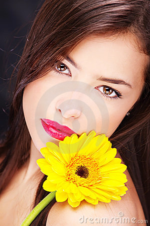 Yellow daisy on woman s shoulder