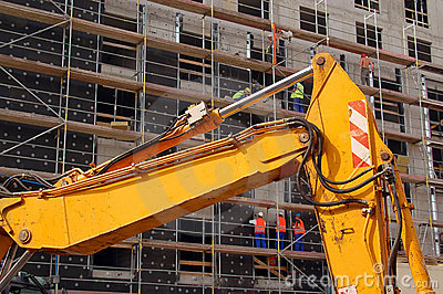 Yellow digger and construction workers