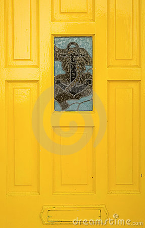 Yellow door with anchor stained glass window