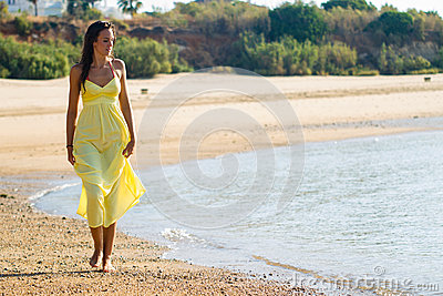 Yellow dress stroll on beach