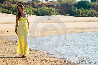 Yellow dress stroll on beach