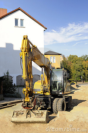 Yellow excavator on the construction site