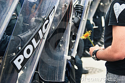 Yellow Flower and Police G8/G20 Protest Editorial Stock Image
