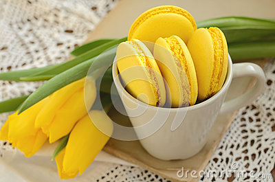 Yellow French macaron and yellow tulips on old book Stock Photo