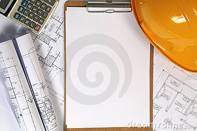 Yellow hard hat and blueprints