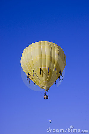 Yellow hot air balloon flying in blue sky