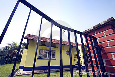 Yellow house behind wrought iron gate