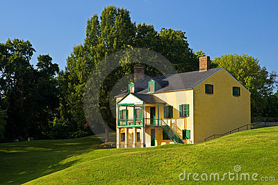 Yellow house on grassy hill