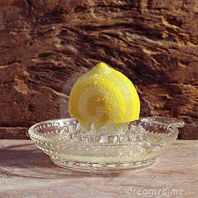 Yellow lemon on a citrus squeezer