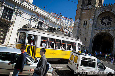 Yellow Lisbon street car by cathedral Editorial Photo