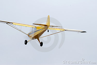 Yellow monomotor airplane low flight