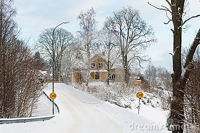 Yellow painted Swedish wooden house in a wintry landscape