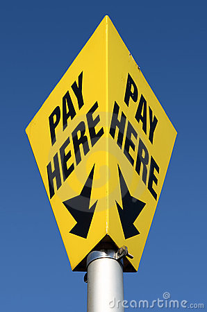 Yellow pay here car parking sign.