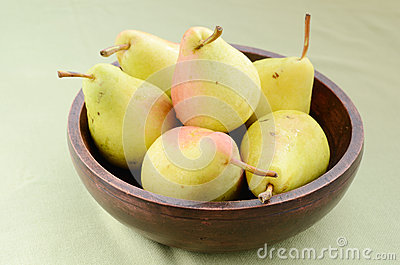 Yellow pears in old wooden bowl