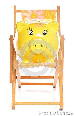 Yellow piggybank on deckchair