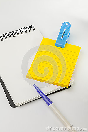 Yellow post note, empty white note, pen and blue clip