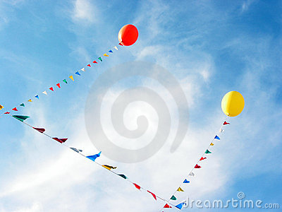 Yellow and red balloons flying in blue sky