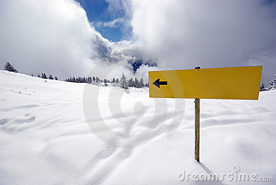 Yellow sign with arrow in mountains