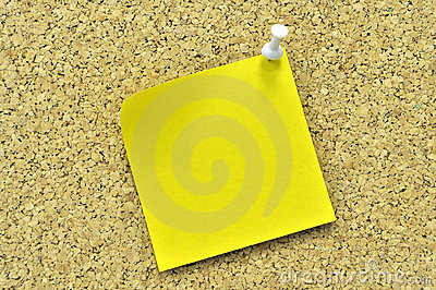 Yellow sticky note on a cork board.