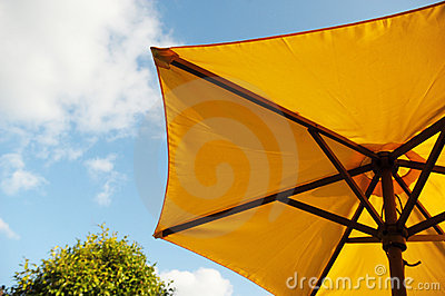 Yellow sun umbrella with sky in background
