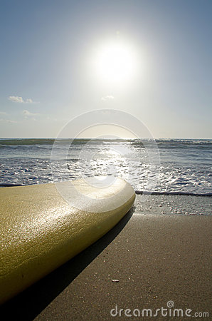 Yellow surfboard on the beach