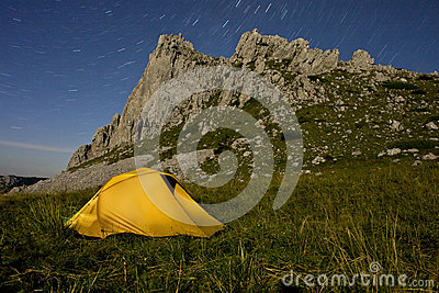 A yellow tent illuminated in mountains