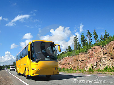 Yellow tourist bus on country highway