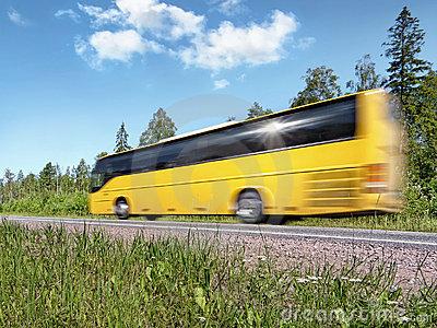 Yellow tourist bus on rural highway, motion blur