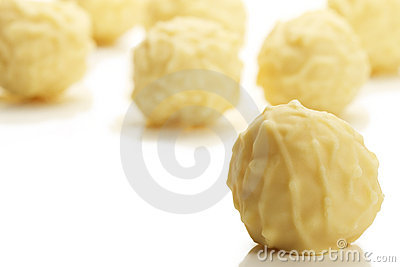 Yellow truffle praline in front of many