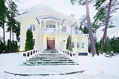 Yellow two-storey cottage with wide front staircase among pines
