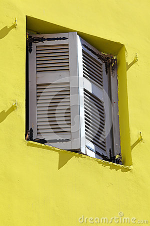 Yellow wall an old window shutters.