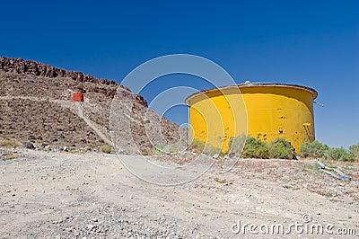 Yellow water tank in desert