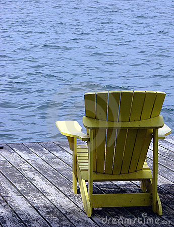 Yellow Wood Adirondack Chair on a Dock over Water