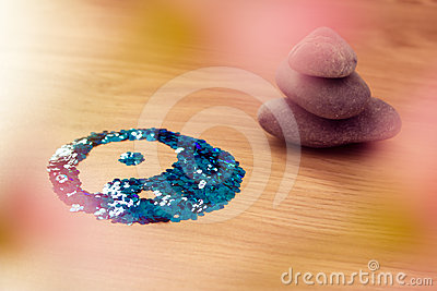 Yin yang symbol on wood with stacked zen stones