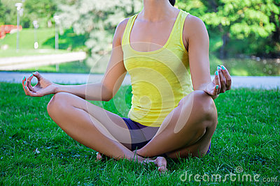 yoga concept  close up of woman sitting in lotus pose in park