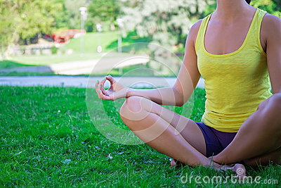 yoga concept  close up of young woman sitting in lotus