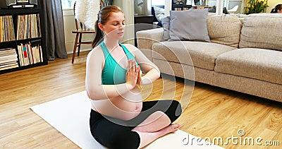 Yoga de pratique de femme enceinte dans le salon banque de vidéos