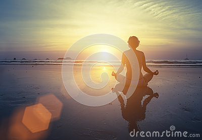 Yoga, fitness and healthy lifestyle. Silhouette meditation girl on the background of the stunning sea and sunset. Stock Photo