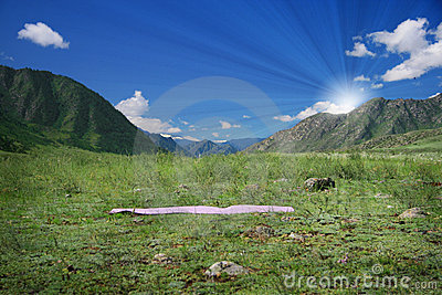 Yoga mat on green field near mountains