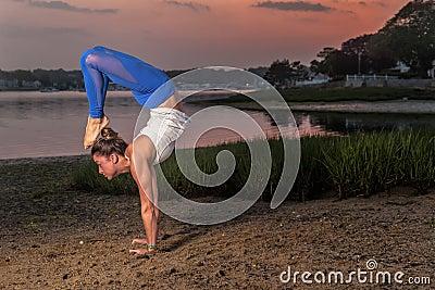 yoga model doing headstand scorpion variation beach stock