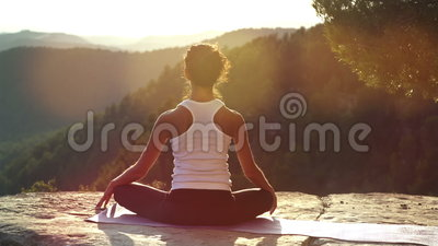 Yoga outside. Beautiful young woman practices yoga moves and positions outdoors on an incredible clifftop setting