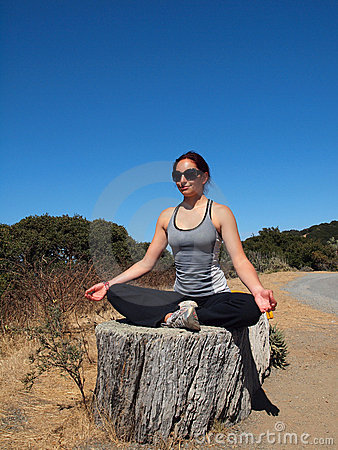 Yoga Superstar lady sits on tree stump, meditates