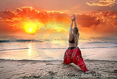 Yoga virabhadrasana warrior pose at sunset