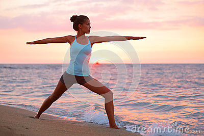 Yoga woman in meditating in warrior pose at beach