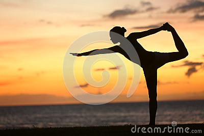 Yoga woman in serene sunset at beach doing pose