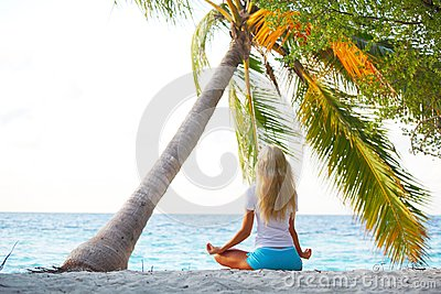Yoga woman under palm