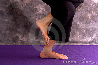 Yoga womans feet in eagle pose asana