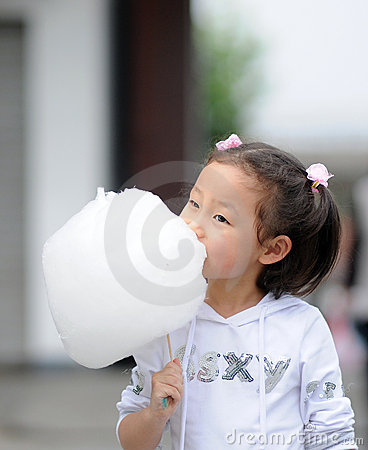 Yong girl eating cotton candy