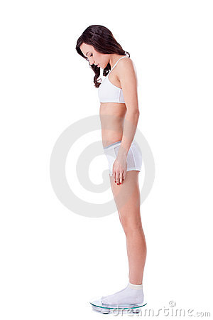 Yound fit girl standing on scales